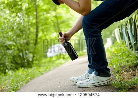 Man depressed with beer bottle sitting on green fence outdoor.