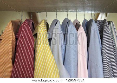 Colorful men's shirts hanging in wardrobe. Set of men's shirts on hangers. Ironed shirts hanging inside the closet.