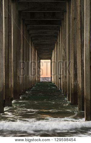 Symmetrical shot under Scripps Pier with waves during sunset in La Jolla, San Diego, California