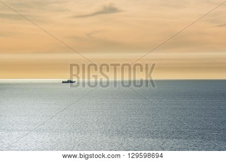 One ship sailing in the pacific ocean with smog and sun ray path during sunset close to San Diego, California