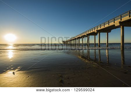 Wide angle shot of Scripps Pier with reflection during sunset with sun in La Jolla, San Diego, California