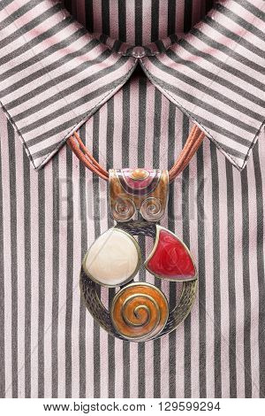 Nacre ethnic pendant on silk striped pink blouse closeup