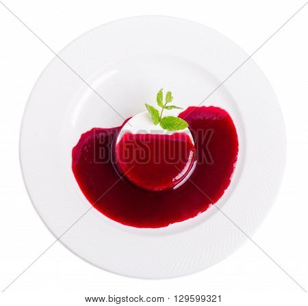 Delicious vanilla panna cotta with raspberry jam and fresh mint. Isolated on a white background.