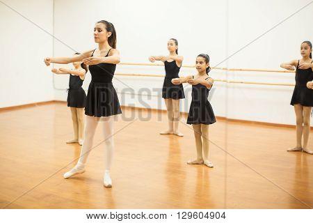 Group of Hispanic girls imitating their teacher during dance class and seen through a mirror