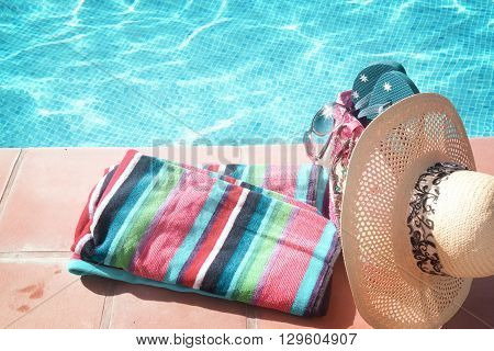 towel and bathing accessories near pool  side,  retro toned