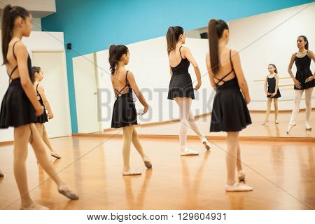 Group of girls in leotards and skirts imitating their teacher during dance class at school