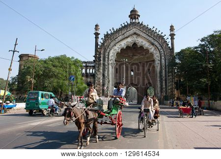 LUCKNOW, INDIA - DEC 19, 2012: Street traffic near the huge famouse gateway Rumi Darwaza at the sunny day on December 19, 2012 in Lucknow India. The gateway was built by Nawab of Lucknow in 1784.