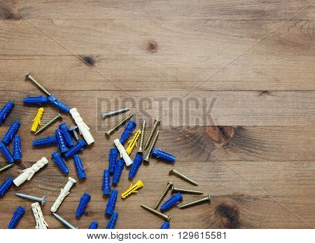screws with blue and yellow dowels on wooden table