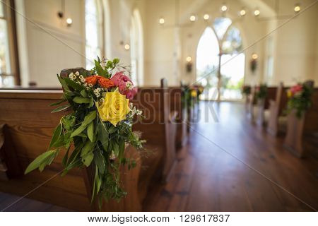 Bouquet hung on pew at wedding, shallow depth of field