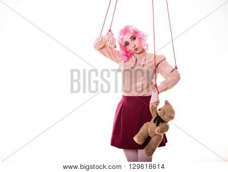 Mental disorder concept. Young woman girl stylized like marionette puppet on string with teddy bear toy isolated on white background
