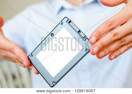 Hands holding fast flash SSD - solid state drive with sata 6 gb connection - blacnk place for diverse informateion and text to be inserted