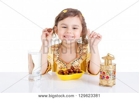 Young Muslim girl eating dates for brakfast in Ramadan - sitting on a table with water dates Quran and Ramadan lantern