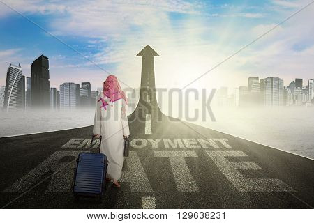 Middle eastern businessman carrying bag and walks on the road with a text of employment rate and upward arrow
