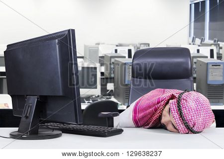Exhausted Arabic worker sleeping in the office while wearing traditional clothes with computer on the table