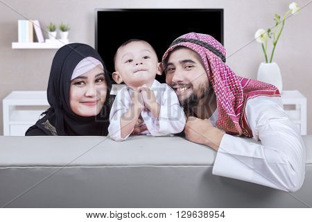Picture of happy middle eastern family sitting on the sofa and smiling at the camera shot in the living room