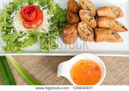 Egg roll or Spring roll or Popiah Vietnamese cuisine in Thai style with sweet suace on wooden table