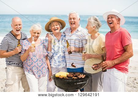 Senior having a barbecue on the beach on a sunny day