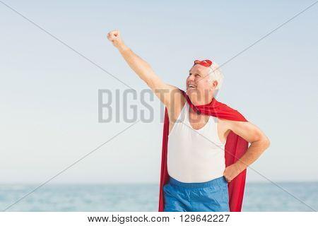 Senior man pretending to be a superhero on a sunny day