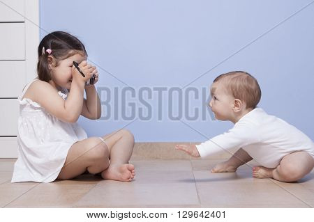 Young girl photographer. Pretty little sister taking pictures to her baby brother with old analog camera