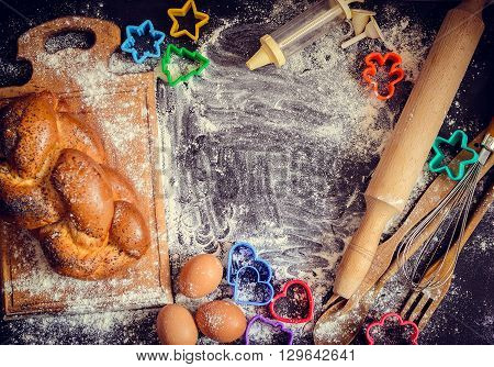 Baking concept on dark background. Baking cookies for children top view of variety of baking utensils with bread eggs and colorful cutters on black chalkboard. Children cooking. Top view.