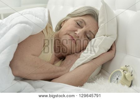 Sleeping senior woman portrait in a bed