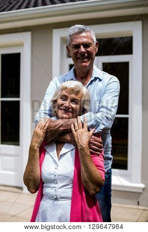Smiling senior couple standing with arms around outside house at yard
