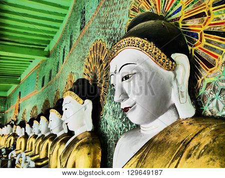 Buddhist terrace (Umin Thounzeh) on Sagaing Hill, Myanmar. A crescent-shaped colonnade of 45 Buddha images showing one in the foregound and the row of statues to the left.