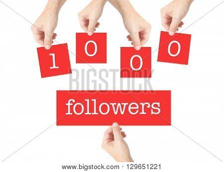 1000 followers written on cards held by hands