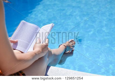 Girl reading a book by the swimming pool