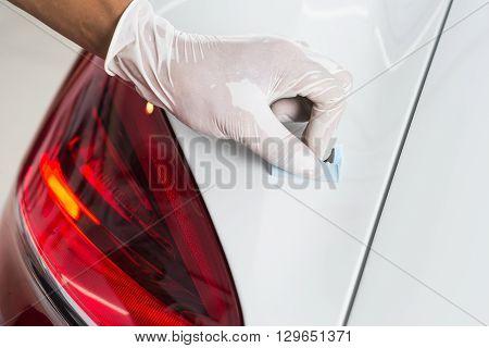 Car detailing series : Closeup of hand  coating white car paint