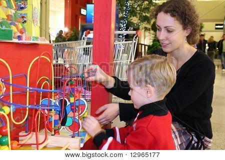mother with child watch toy in shop