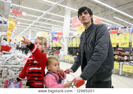 father with children in shop