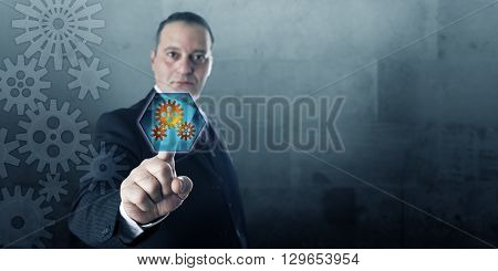 Engineer connecting to a virtual gear drive via a push button displaying cog wheels. Business process management metaphor and industrial technology concept. Plenty of copy space over gray stone wall.