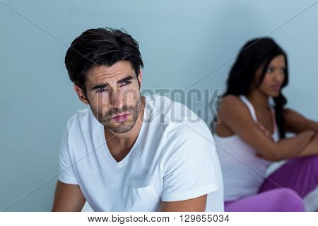 Upset couple ignoring each other after fight on bed in bedroom