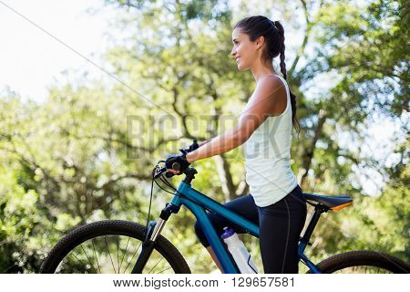 Woman smiling and posing with her bike on the wood