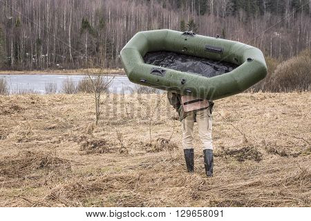 man carries a rubber inflatable boat on the shore of the lake located near the forest in order to go fishing