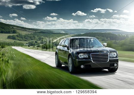 Saratov, Russia - August 9, 2015: Black car Chrysler 300c speed drive fast on the asphalt road at daytime