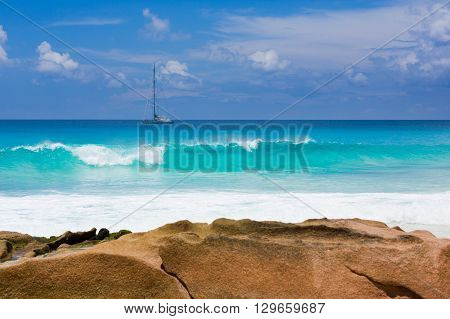 Seychelles beach with granite rock, turquoise water with sailing ship