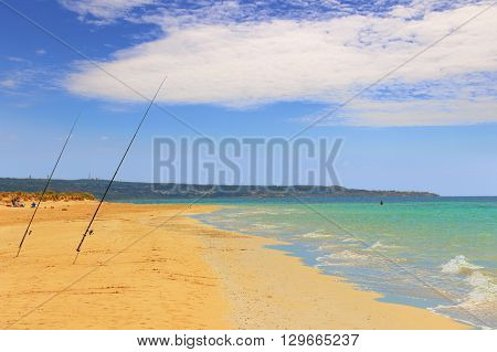 The most beautiful sandy beaches of Apulia. ITALY(SALENTO).From Torre Pali to Pescoluse the shore is made of a so fine white sand and vashed by a so clear sea that it is called 'Maldive of Salento'.Location of a fisherman: fishing poles stuck in the sandr