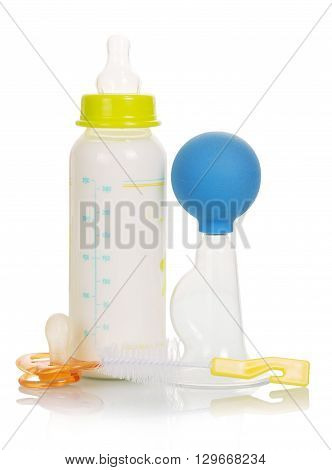 Breast pump, baby bottle with milk and brush isolated on white background