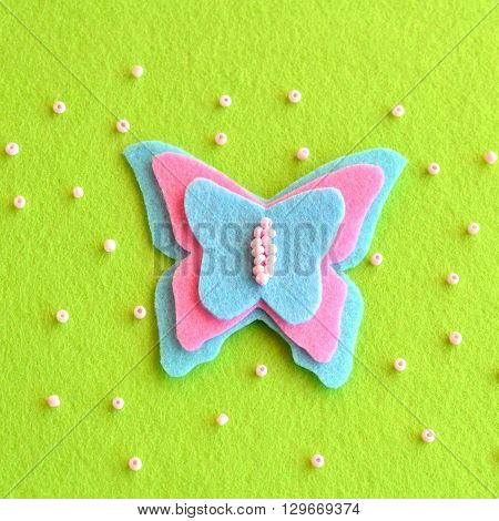 Felt butterfly on a green background, beads. Simple children's crafts