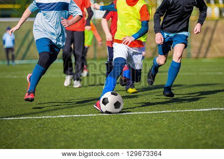 Football soccer game of youth teams. Running young players kicking soccer ball