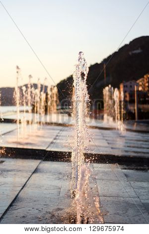 A stream of water in a modern fountain. The water refracts sunlight sunset.