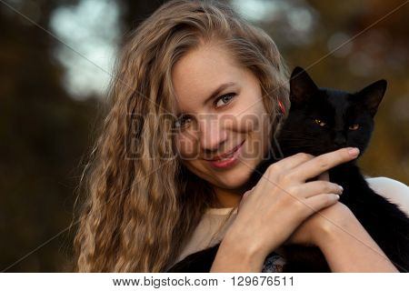 Beautiful, attractive, nice, pretty girl with long, curly, wavy hair hug nice cat, black cat, lovely cat with green eyes, mysterious cat. Pretty, cheerful, smiling, happy girl with cat, girl hold cat in hands, cat.