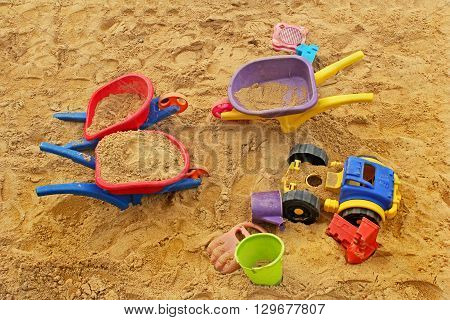 Multicolored wheelbarrows and other toys left behind in a sandbox.