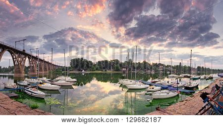 Sunrise on the river with yachts in purple colors. Central embankment  Dnepropetrovsk city, Ukraine in summertime.