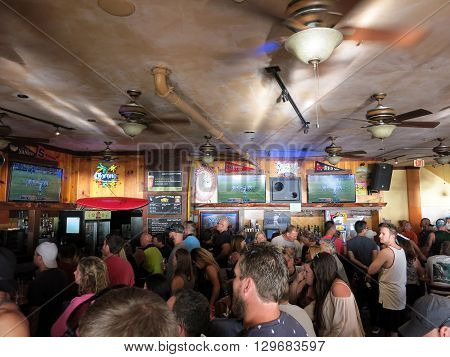 WAIKIKI OAHU - FEBRUARY 7: Crowd People watch Superbowl 50 game at iconic Lulu's Bar. SupeBowl commercials cost roughly $4.5 million a piece taken February 7 2016 Waikiki Hawaii.