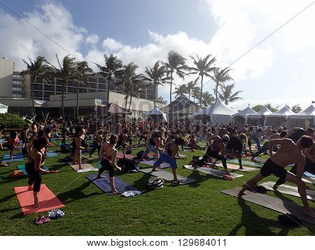 NORTH SHORE HAWAII - FEBRUARY 25: People do side angle pose Utthita Parsvakonasana at outdoor yoga class facing stage at Wanderlust yoga event on the North Shore Hawaii on February 25 2016.