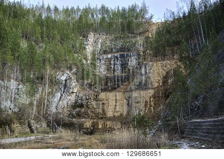 Abandoned talc quarry overgrown with trees and grass