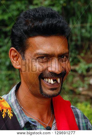 KANDY, SRI LANKA - DECEMBER 5, 2008: Toothless Ceylonese street vendor smiles in the street of the town